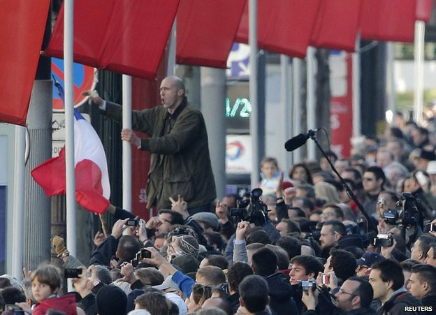 A protester shouts slogans as President Hollande passes on the Champs-Elysee, Paris, 11 November