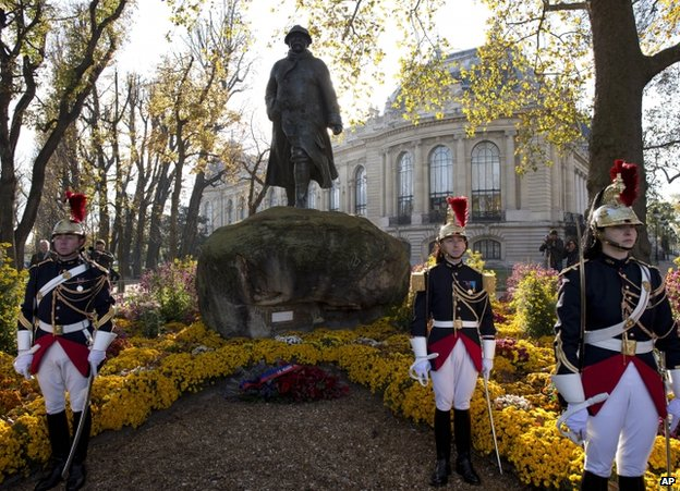 Republican guards stand in front of a statue in Paris of French President Georges Clemenceau, who led the nation into WWI, 11 November