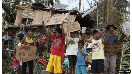 Children hold signs asking for help and food