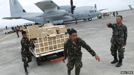 Military personnel deliver aid at the destroyed airport in Tacloban