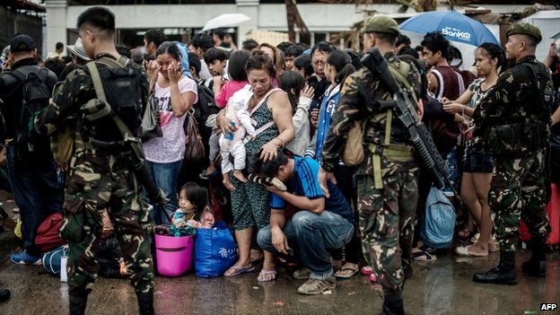 A woman holding a baby comforts a crying relative as a plane leaves the airport during evacuation operations in Tacloban, on the eastern island of Leyte on 12 November 2013
