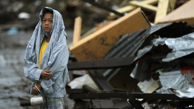 A young boy waits at the side of the road for fresh water surrounded by debris from Typhoon Haiyan in Tacloban, central Philippines, 12 November 2013