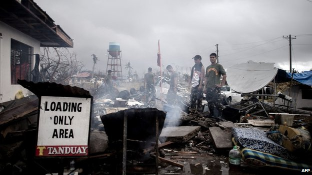 Filipino military personnel stand by a building damaged by typhoon Haiyan at the airport in Tacloban, on the eastern island of Leyte on 12 November 2013