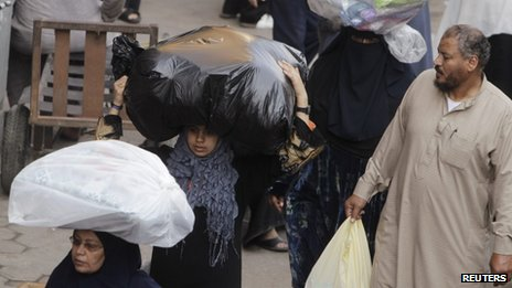 Women carry clothes bought at al-Ataba, a popular market in downtown Cairo November 11, 2013