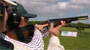 Person being coached in shooting shotgun