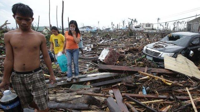 Survivors walk along debris from damaged homes at typhoon ravaged Tacloban