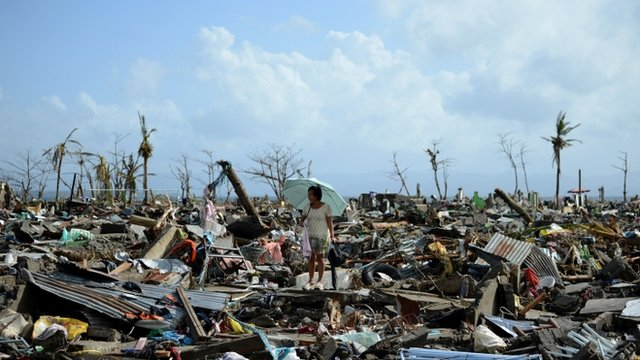 A woman stands amid the debris in Tacloban