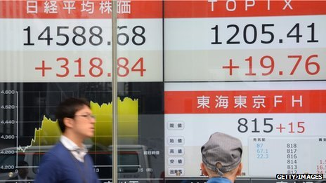 Man walks past Japanese stock market boards in Tokyo on 12 November