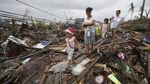Survivors walk in typhoon ravaged Tacloban city in the Philippines