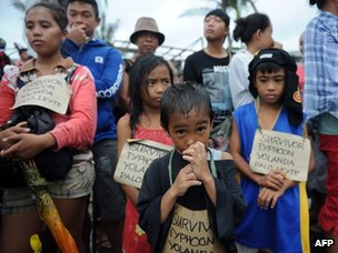 Young survivors of Typhoon Haiyan wait to be evacuated on a military plane at Tacloban airport, Leyte province, in the central Philippines, on Tuesday