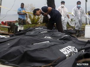 A woman searches for missing loved ones in bodybags in Tacloban city, devastated by Typhoon Haiyan, in the central Philippines on Tuesday