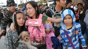 A mother cries after her family failed to get a flight on a C-130 military plane out of Tacloban, Leyte province, central Philippines on Tuesday, as hundreds of residents try to leave the city due to an approaching tropical storm