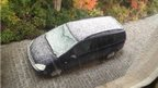 A car with white hail stones over it.