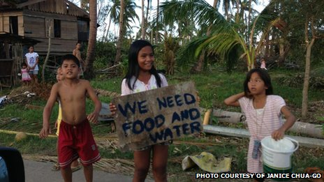 "Children on the way to northern Cebu holding up a sign saying ""We need food and water"""
