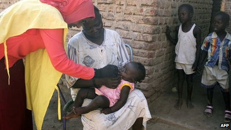 A social worker (L) gives a polio drop to a child from al-Muniera village in Madani, the capital of al-Jazirah state in east-central Sudan (18 November 2007)