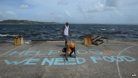 "A man paints a message on a basketball court that reads ""Help SOS We Need Food"" at Anibong in Tacloban, eastern island of Leyte on 11 November 2013"