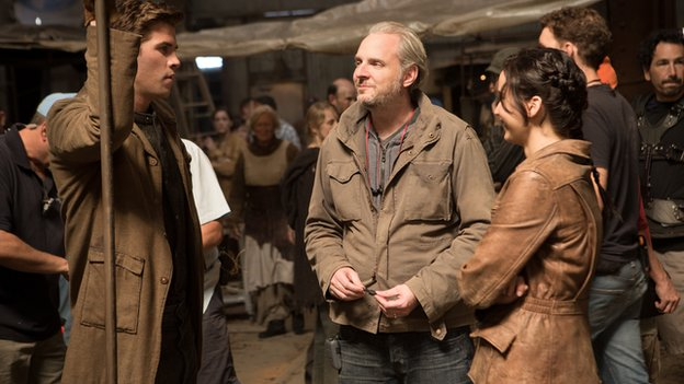 Director Francis Lawrence (centre) on set with Liam Hemsworth (left) and Jennifer Lawrence (right)