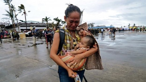 A woman is evacuated from the Philippine island of Leyte after the typhoon, 12 November 2013