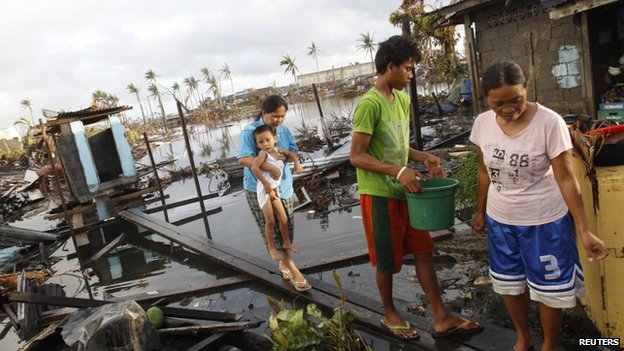 Rea Canibel carries her child as she walks on a plank across dirty water, at what is left of their home after super typhoon Haiyan battered Tacloban City, in central Philippines 13 November 2013