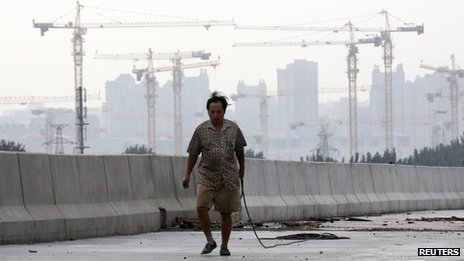 A worker carries a rope at a construction site for a new road in Beijing on 1 August 2013