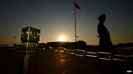 A Chinese paramilitary officer patrols Tiananmen Square in front of the Great Hall of the People (background) after the Communist Party Central Committee concluded its secretive Third Plenum in Beijing on 12 November 2013