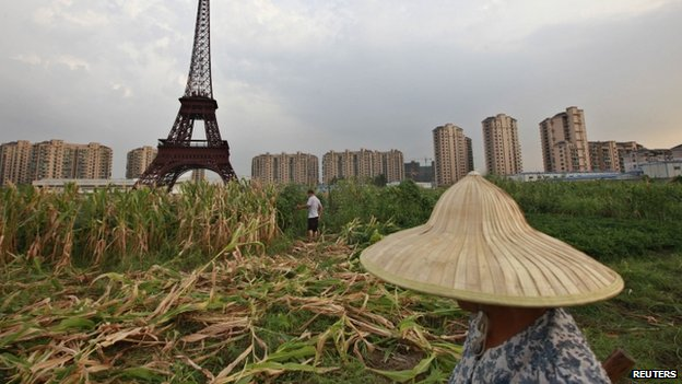 A farmer walks through a corn field near a replica of the Eiffel Tower at the Tianducheng development in Hangzhou, Zhejiang province, in this 1 August 2013 file photo