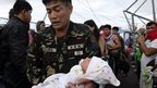 A soldier carries one-day-old baby Ian Daniel Honrado to a waiting military transport plane from Tacloban airport, Tacloban, Leyte, 13 November 2013