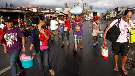 People standing in the wreckage caused by Typhoon Haiyan in the Philippines