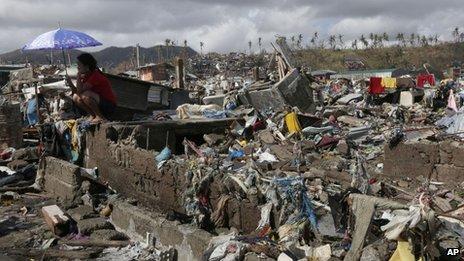A survivor sits among debris in Tacloban, Leyte province