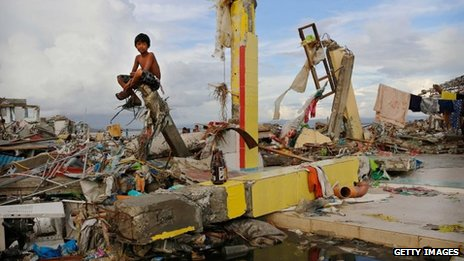 A young boy sits on the ruins of a building amid scenes of devastation in the aftermath of Typhoon Haiyan in Tacloban, Leyte, Philippines