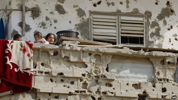 Children on the balcony of a building damaged during the November 2012 Israel-Gaza conflict (13 November 2013)