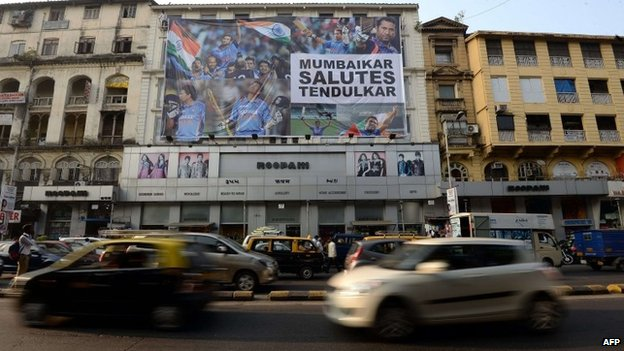 Vehicles journey past a huge banner saluting Indian cricketer Sachin Tendulkar on the facade of a shop in Mumbai on November 13, 2013