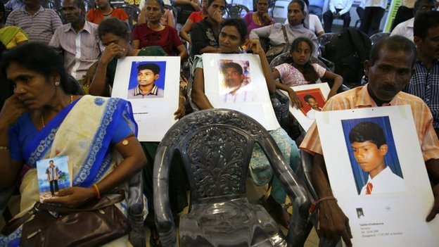 People belonging to the Sri Lankan minority Tamil ethnic group hold up photos of their relatives who disappeared during the Sri Lankan civil war