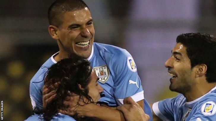 Uruguay's defender Maxi Pereira (C) celebrates with his teammates Edison Cavani (L) and Luis Suarez
