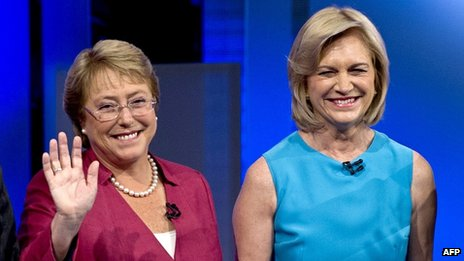 Chilean presidential candidate Michelle Bachelet, of the New Majority Coalition waves next to Evelyn Matthei, of the right-wing Democratic Independent Union party, during a presidential candidate debate on 29 October, 2013