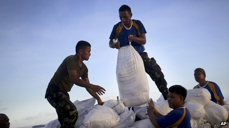 Soldiers moving bags of food aid at an airport in the Philippines