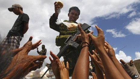 A soldier hands out food to a crowd. People's hands are outstretched towards him