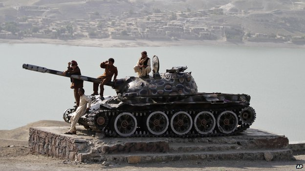 Afghan men sit on top of an old Soviet tank overlooking Naghlu lake on the outskirts of Kabul, Afghanistan (11 Sept. 2013)