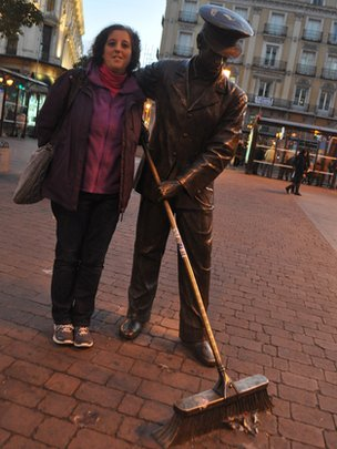 Julia Toledo and a statue of a street-sweeper in Madrid