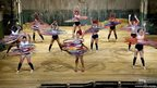 A group of dancers on a grand theatre stage spinning hula hoops around their waists. Each dancer has about 20 colourful hoops.