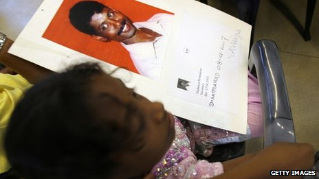 A Tamil girl holds up a photograph of her father who disappeared during the Sri Lankan civil war