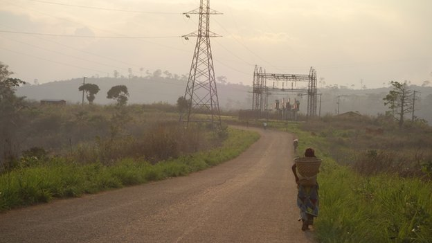 A person walking past power lines near Inga dam, DR Congo