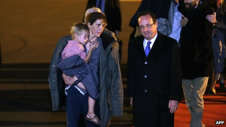 French President Francois Hollande (front R) speaks to Albane Moulin-Fournier carrying one of her children as the seven members of the Moulin-Fournier family arrive from Yaounde, at the Orly airport, near Paris (20 April 2013)