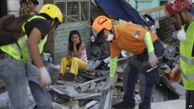 A woman sits amid debris as Filipino rescue workers clear debris from a street in Guiuan, Philippines, 15 November 2013