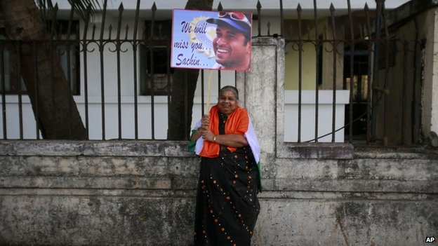 An Indian woman holds a placard of Indian cricketer Sachin Tendulkar as she arrives to watch Tendulkar's last test match in Mumbai
