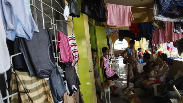A family and their pet dogs sit in the balcony of a school compound used as a temporary shelter for survivors after the Super typhoon Haiyan battered Tacloban city in central Philippines