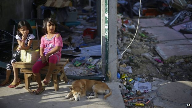 Young girls sit near a dog in an area badly affected by Typhoon Haiyan in Guiuan on 15 November 2013