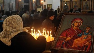 A Syrian woman lights candles as she attends Mass at the Mar Elias (St Elijah) Orthodox church in Bab Touma, Damascus (24 December 2012)