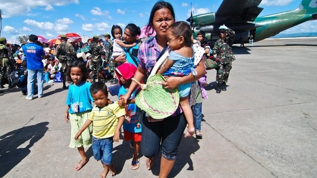 Survivors wait for a military plane that will carry them to Manila at Tacloban airport on November 15, 2013 in Leyte