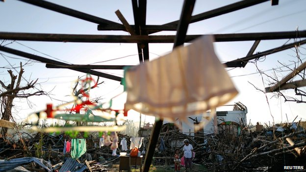 Typhoon survivors outside the ruins of their home, Tacloban (15 Nov)